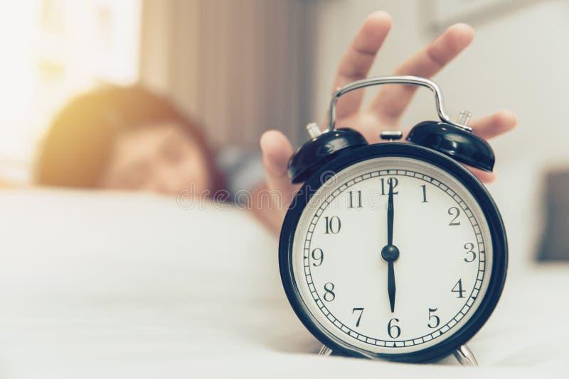 Ленивый проспать вверх по руке девушки с кольца будильника на кровати стоковые изображения rf