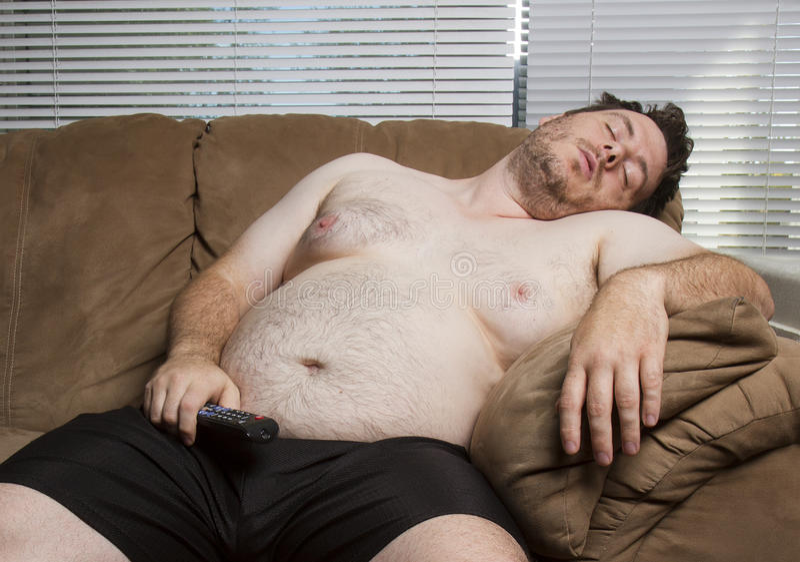Ленивый тучный парень смотря ТВ стоковое изображение rf