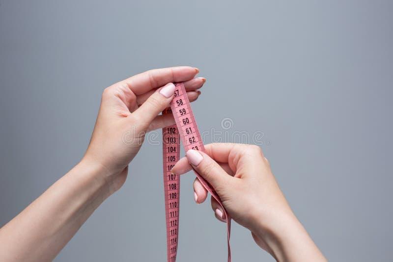 Лента в женских руках на серой предпосылке Потеря веса, диета стоковые фотографии rf