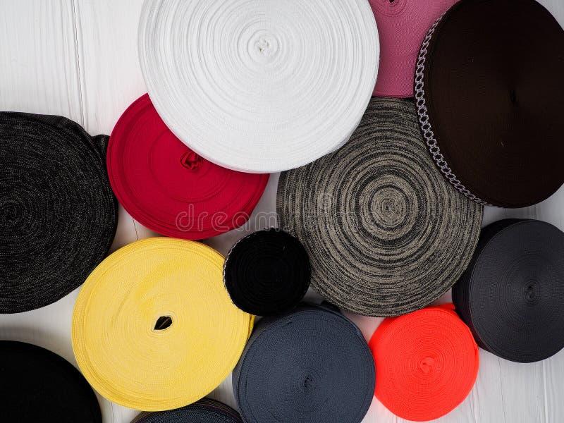 Лента других цветов в катушках, много пестротканых катушек для текстильной промышленности, производства одежды стоковое фото