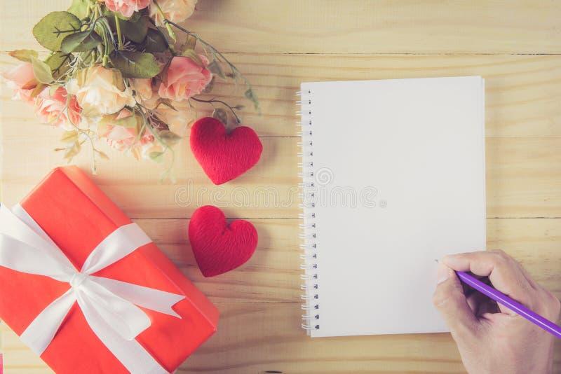 Лента и сердце смычка подарочной коробки белые вручают держать карандаш с тетрадью стоковые изображения