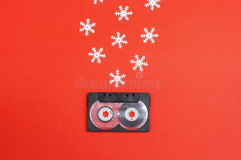 Лента магнитофонной кассеты с декоративными снежинками на красной предпосылке Музыка для настроения рождества стоковое фото