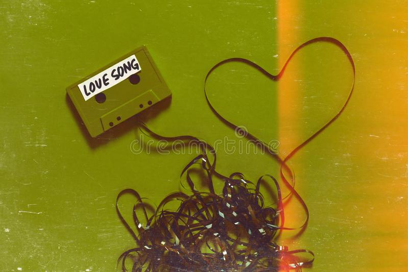 Лента магнитофонной кассеты с песня о любви надписи и сердце на зеленой предпосылке Концепция ретро технологии Romance с Scratche стоковая фотография