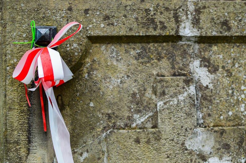 Лента с национальными цветами Польши связала до старого могильного камня на кладбище ols Вся концепция дня Святых стоковое фото