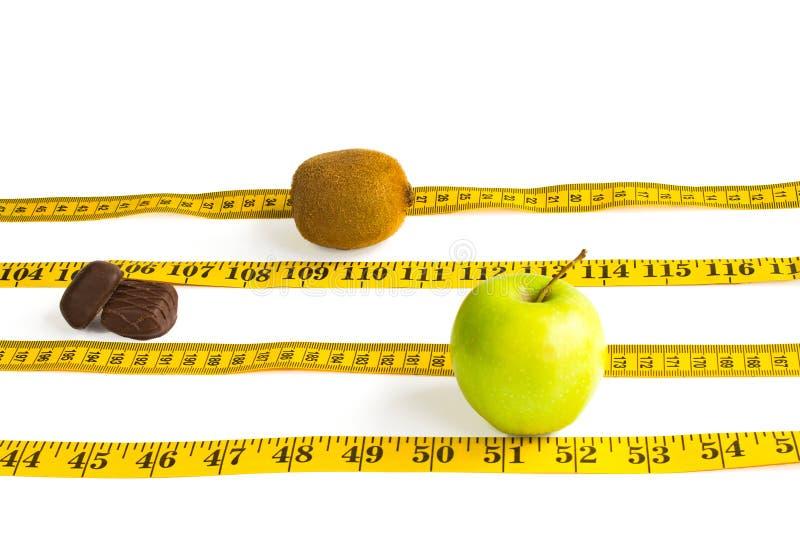 Лента, яблоко, корки и киви измерения изолированные на белизне стоковые фото