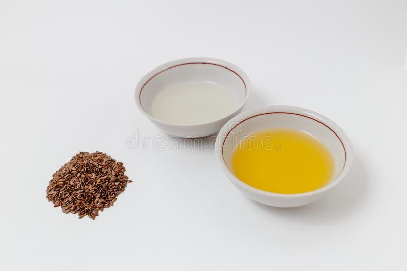 Лен и подсолнечное масло на белой предпосылке стоковая фотография