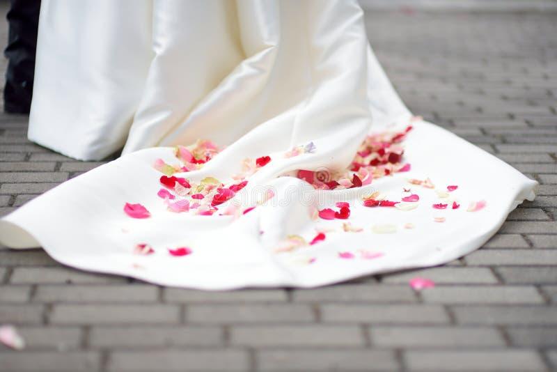 Лепестки розы на платье свадьбы стоковая фотография
