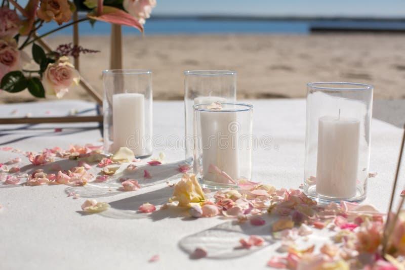 Лепестки свежего цветка лежат на поле рядом с украшенным сводом свадьбы и белыми свечами r стоковая фотография rf