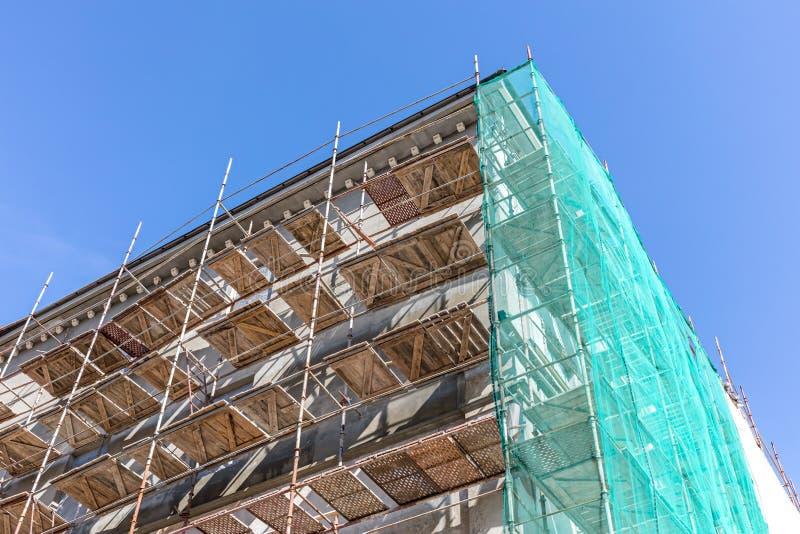 Леса для строя реновации фасада против голубого неба стоковые фотографии rf