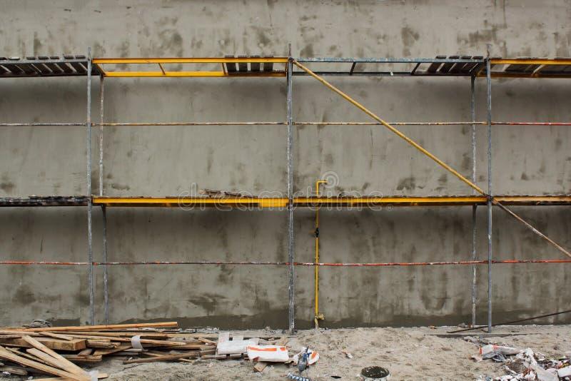 Леса на строя бетонной стене Система лесов в конструкции стоковые изображения rf