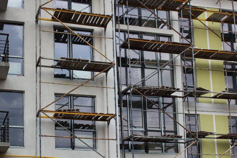 Леса на строя окнах facadewith Система лесов в конструкции стоковые изображения