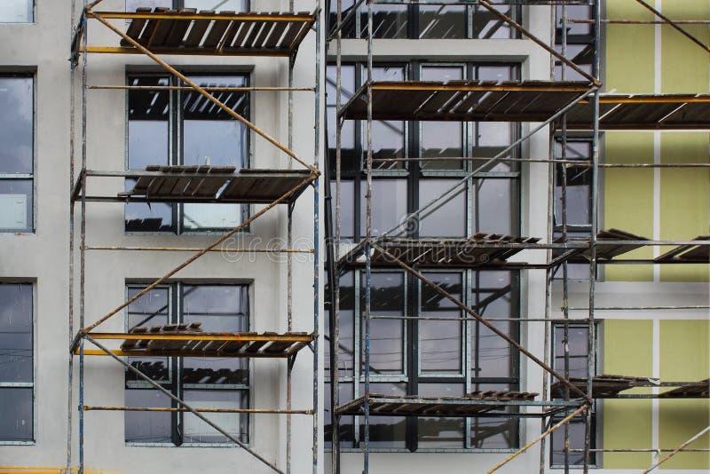 Леса на строя окнах facadewith Система лесов в конструкции стоковое изображение rf