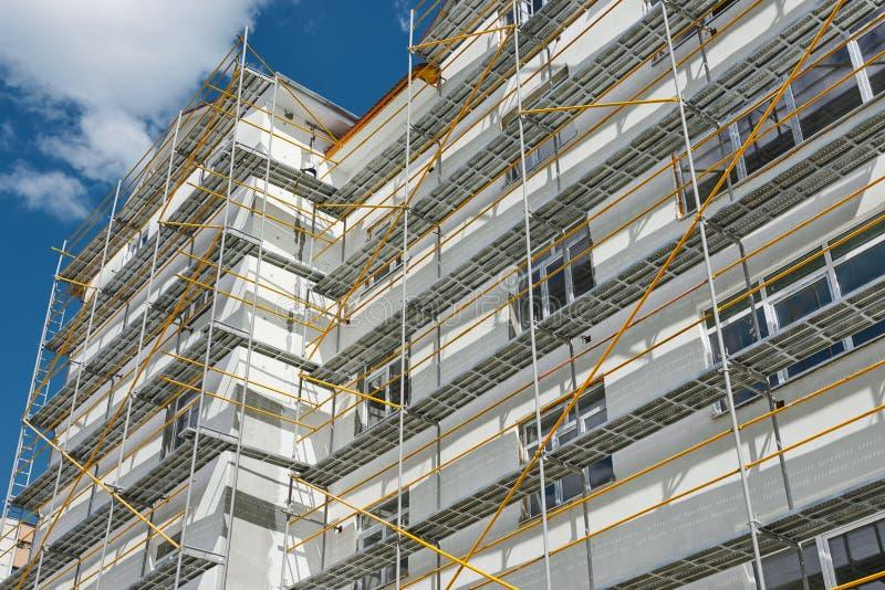 Леса около нового дома, строя экстерьера, индустрии конструкции и ремонта, белой стены и окна, желтой трубы стоковое изображение rf