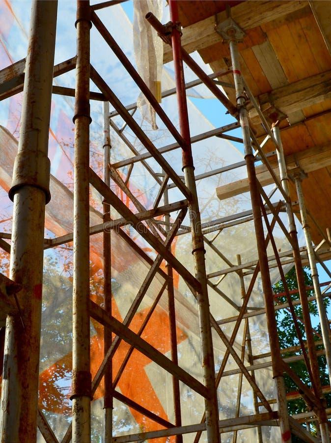 Леса перед отремонтированным зданием положены в кожух с сетью безопасности конструкции, взглядом from inside, солнечный день осен стоковое изображение