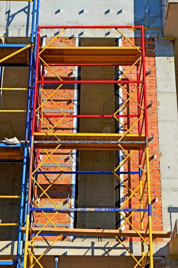 леса - поднятая структура красочных поляков металла и деревянных доск для архитектуры repair) , строительная площадка, стоковая фотография