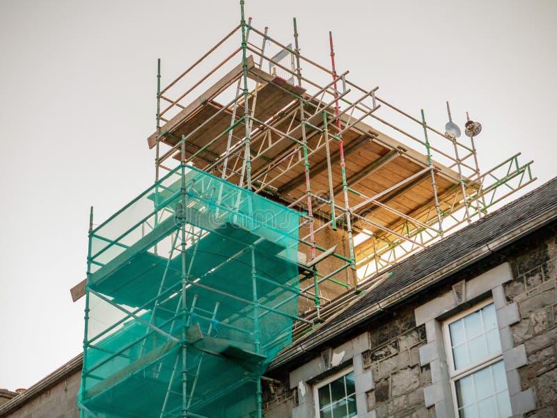 Леса установили на старый дом для того чтобы отремонтировать камин Концепция и технология строительного бизнеса стоковые изображения rf
