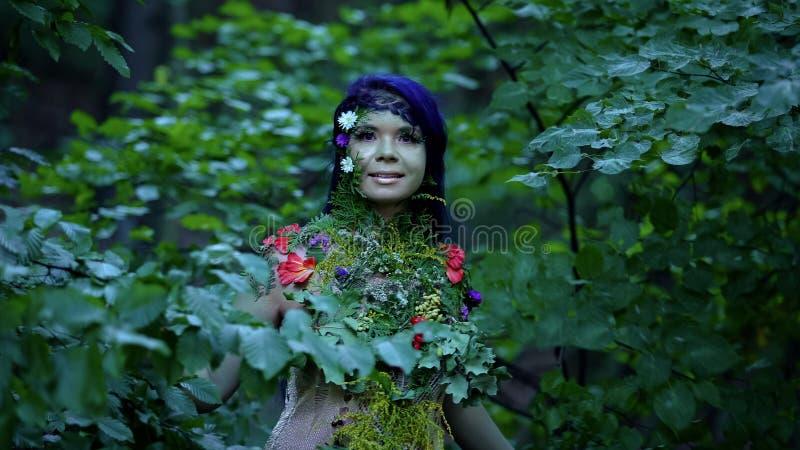 Лесная нимфа среди деревьев, смотрящих на камеру, природный дух, мифология, весна стоковое фото