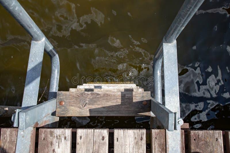 Лестница металла на деревянной пристани Спуск к воде на озере стоковые фотографии rf