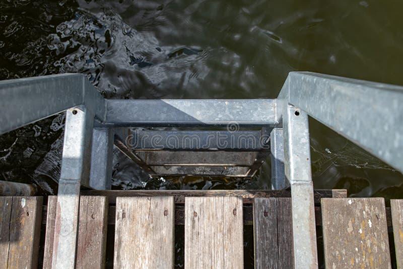 Лестница металла на деревянной пристани Спуск к воде на озере стоковое фото rf