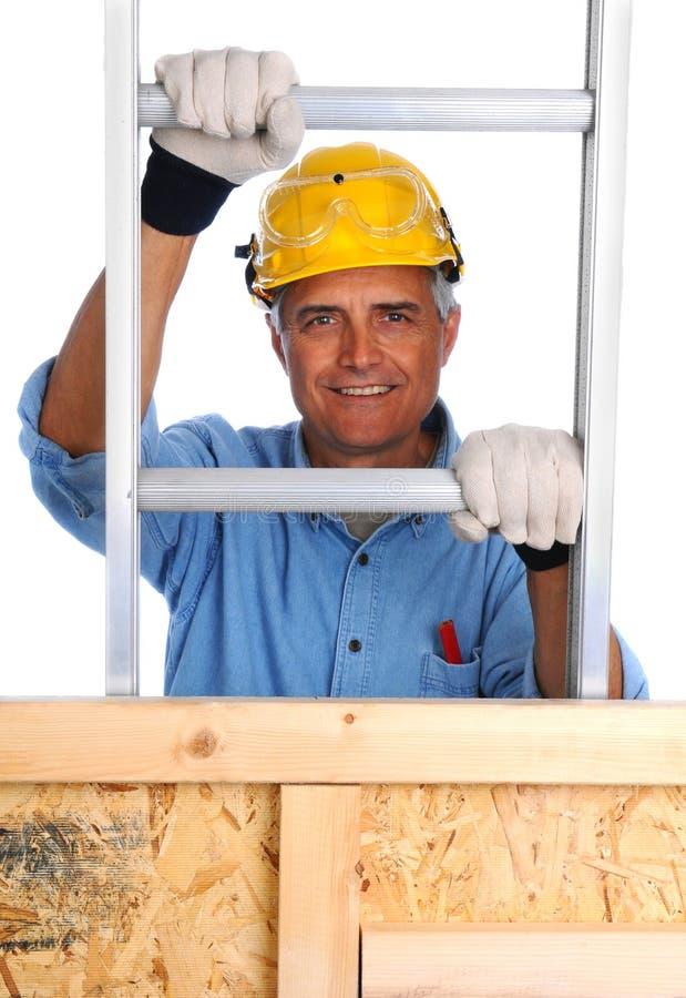 Лестница рабочий-строителя взбираясь стоковое фото