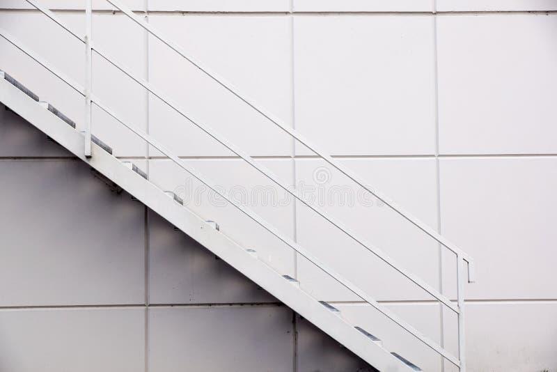 Лестница стальной фабрики, лестница пожарного выхода перед серебряной стеной металлического листа стоковая фотография