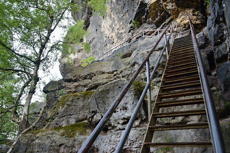 Лестницы с прокладывая рельсы водить к верхней части замка Zirkelstein в Saxon Швейцарии в тени во время захода солнца лета в июн стоковые фотографии rf