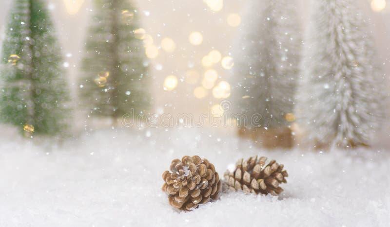 Лес зимы со светами bokeh гирлянды конусов сосны снега морозных елей падая золотыми Плакат поздравительной открытки Нового Года р стоковая фотография