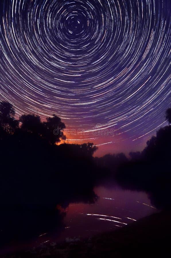 Лес и озеро ночи на звезде предпосылки отстают стоковые фото