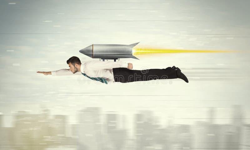 Летание бизнесмена супергероя с ракетой пакета двигателя над cit стоковое фото