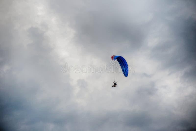 Летание Гая на ясно голубом небе змеем paramotor красным, весьма портом деятельности стоковые фото