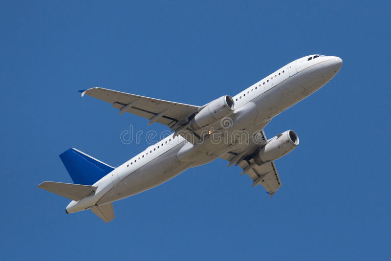 Летание коммерчески самолета в голубом небе стоковое фото