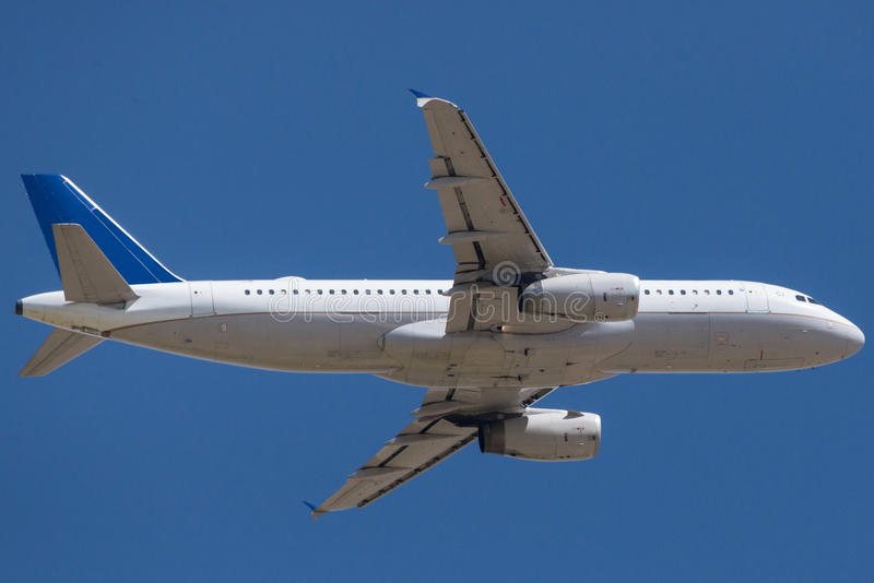 Летание коммерчески самолета в голубом небе стоковая фотография