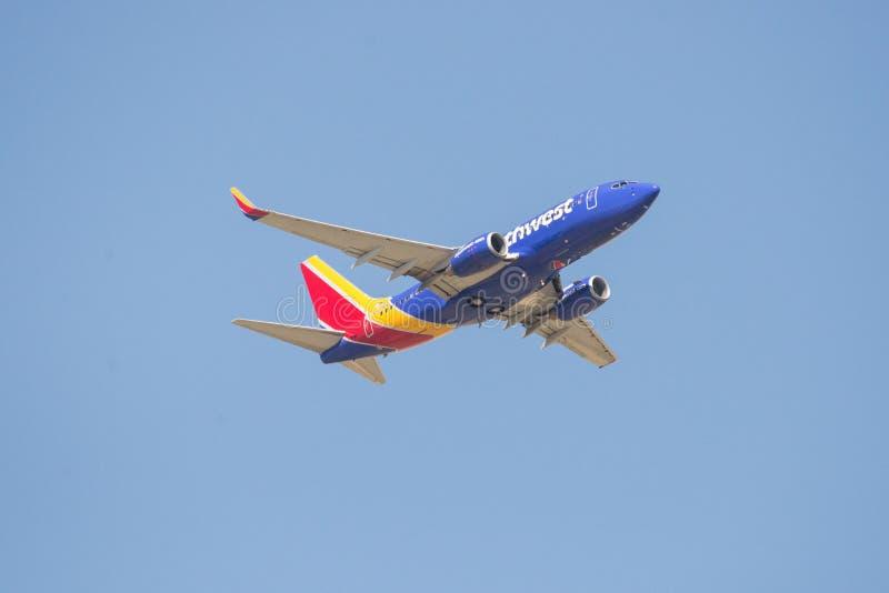 Летание коммерчески самолета в голубом небе стоковое фото rf