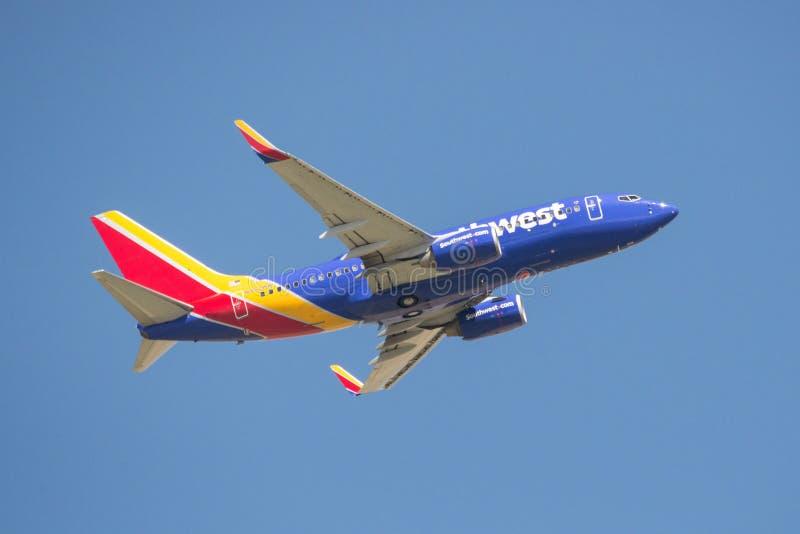 Летание коммерчески самолета в голубом небе стоковые фото