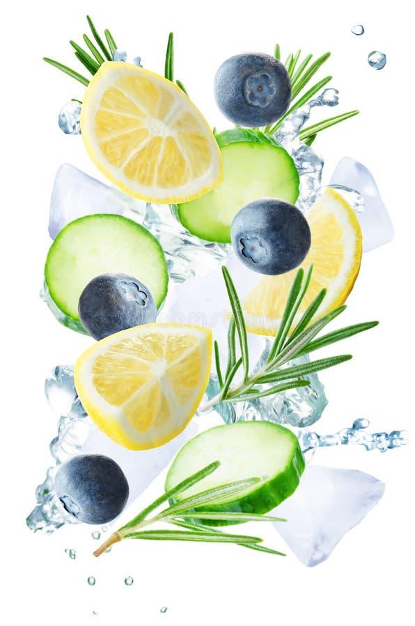 Летание лимона, огурца, голубики и розмаринового масла с льдами и wat стоковые фотографии rf