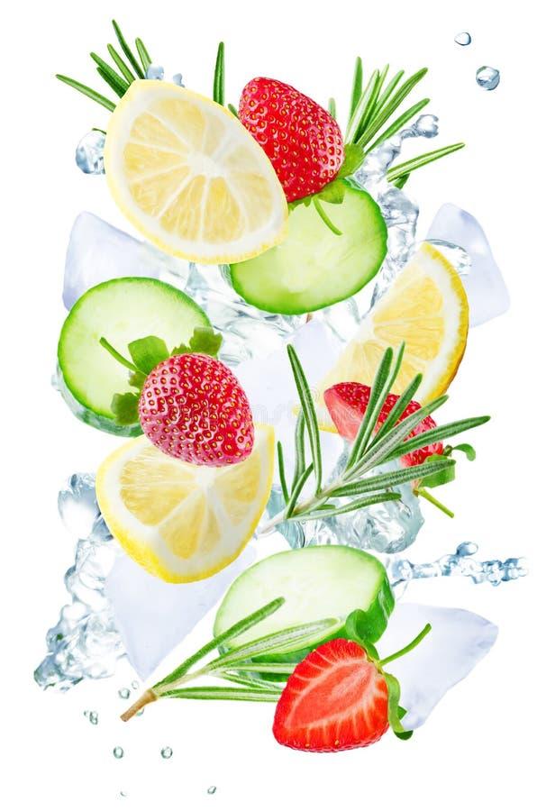 Летание лимона, огурца, клубники и розмаринового масла с льдами и wa стоковые изображения rf