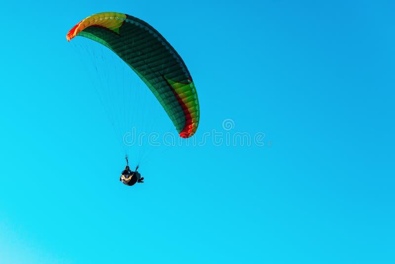 Летание параплана на красочном парашюте в голубом ясном небе на ярком солнечном летнем дне Активный образ жизни, весьма спорт Сво стоковое изображение