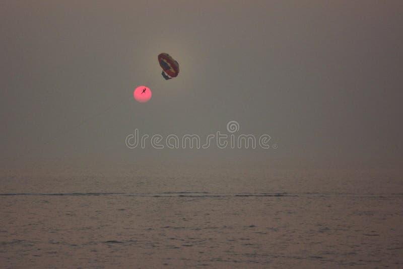 Летание параплана против заходящего солнца стоковое фото rf