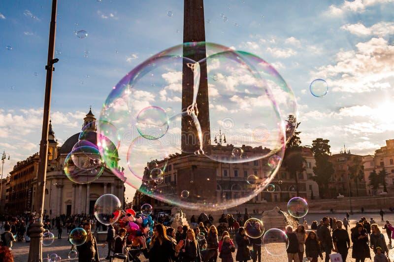 Летание пузырей мыла на Аркаде del Popolo, квадрате людей в Риме полном счастливых положительных людей, туристов и locals с римск стоковое фото