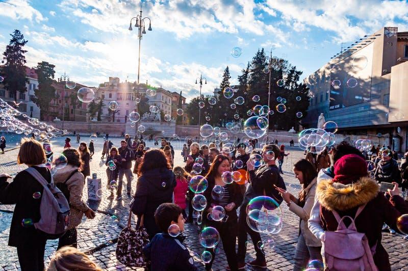 Летание пузырей мыла на Аркаде del Popolo, квадрате людей в Риме полном счастливых положительных людей, туристов и locals с римск стоковое изображение rf