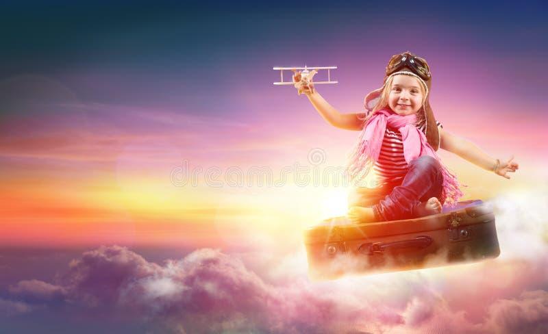 Летание ребенка с фантазией на чемодане стоковые фото
