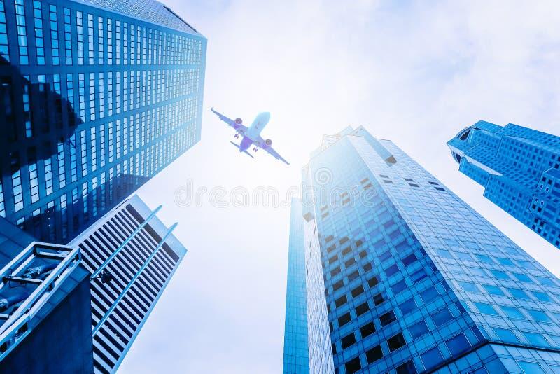 Летание самолета над современным стеклом и стальными офисными зданиями в Сингапуре стоковая фотография