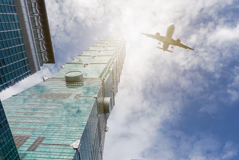Летание самолета над highrise современными офисными зданиями Тайбэем 101 на Тайване стоковое фото rf