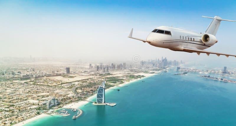 Летание самолета частного самолета над городом Дубай стоковое фото