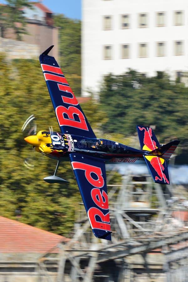 Летание самолета Kirby Chambliss против предпосылки зданий стоковое изображение