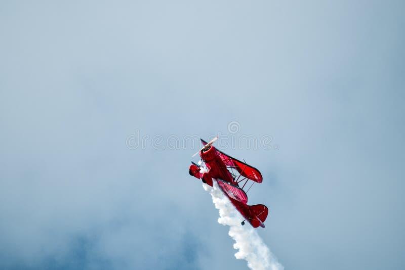 Летание самолет-биплана верхнее с дымом приходя из двигателей стоковая фотография