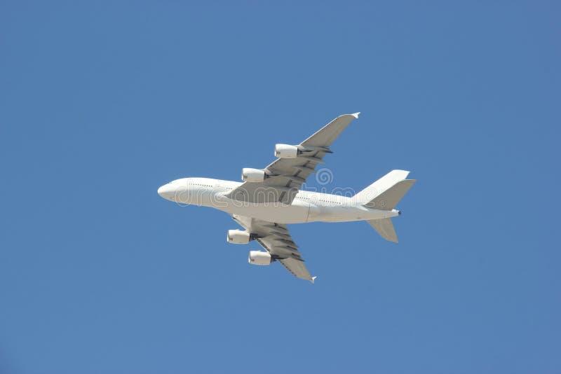 Летание самолета на ярком голубом небе стоковое изображение rf