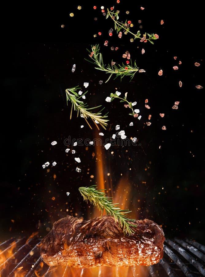 Летание специй и соли барбекю над литым железом скрежещет с пламенами огня стоковое изображение rf