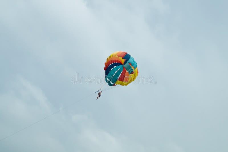 Летание Skydiver с красочным парашютом на предпосылке неба стоковые изображения rf