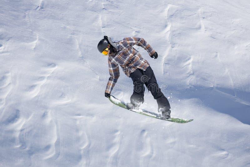 Летание Snowboarder на предпосылке снежного наклона Весьма спорт зимы, сноубординг стоковые фотографии rf